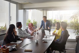 Male professional presenting to coworkers at meeting