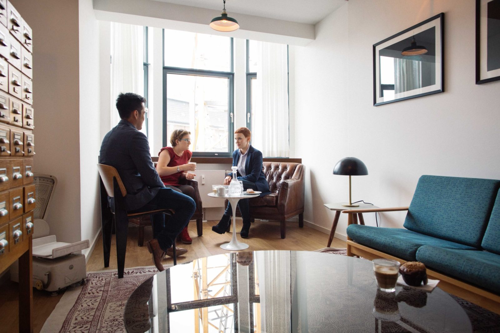 Three Young People Chatting Over Coffee In Bright Minimalist Design Lounge