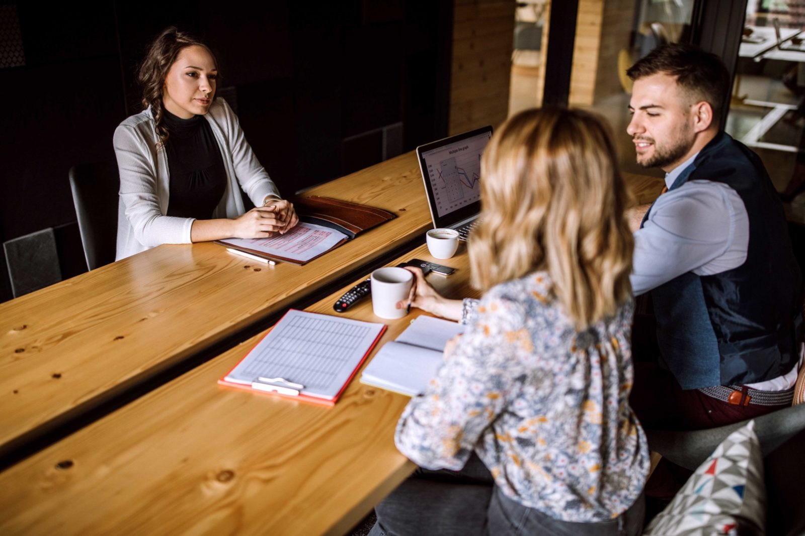 Man accompanied with two women sitting in board room and having business interview