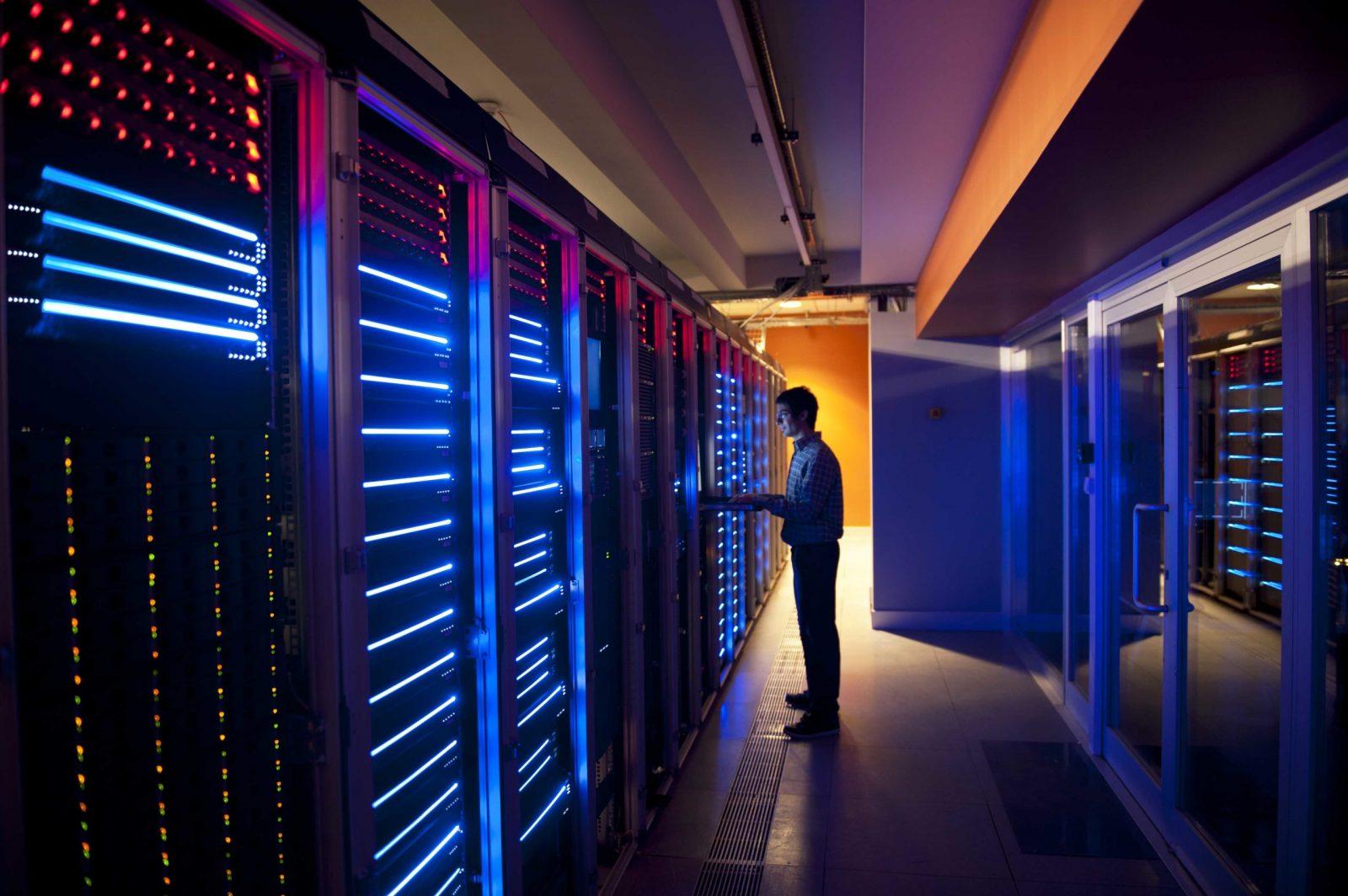 Modern interior of server room in datacenter. IT Engineer in Action Configuring Servers