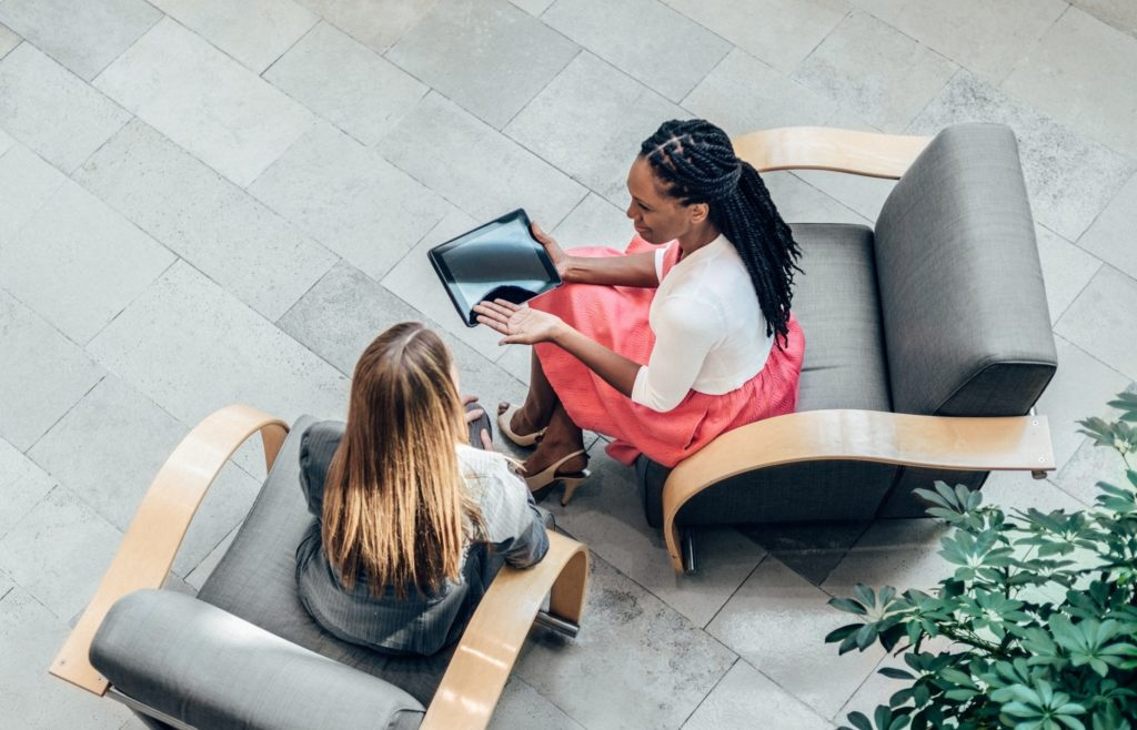 Overhead view of two business women having a meeting in an Office Lobby