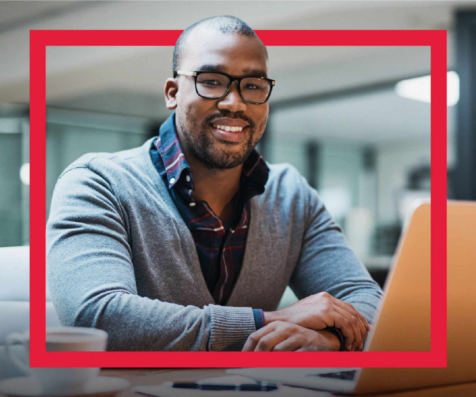 A Black developer wearing glasses smiles and sits in front of a laptop