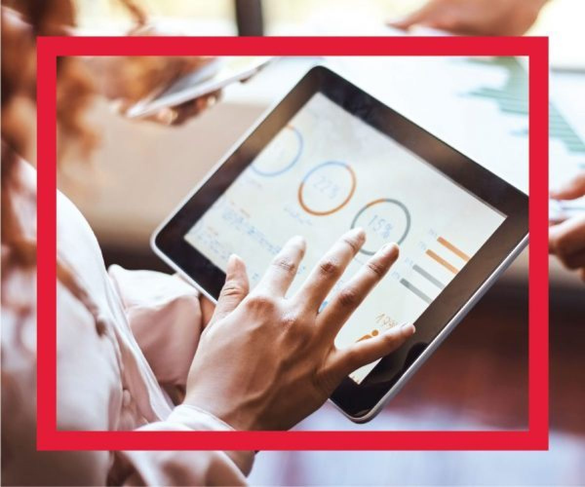 Hands holding ipad with data graphics on display