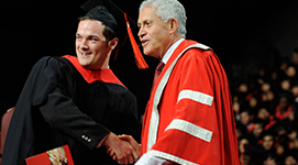 York U's President Mamdouh Shoukri shaking hands with a student during convocation